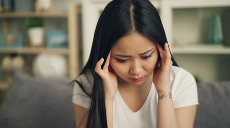 dor de cabeça : Unhappy Asian female student is feeling bad having headache and trying to release pain massaging her head touching temples with sad face. Sick youth concept. Stock Footage