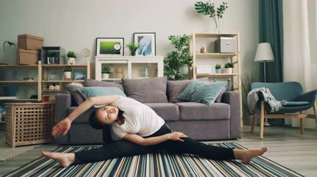tornász : Beautiful young lady is doing physical exercises at home stretching legs and body sitting on floor of stylish modern apartment. Sports and millennials concept.