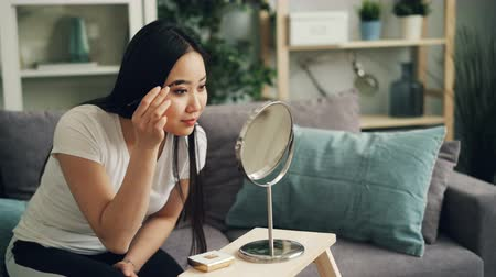 装飾品 : Good-looking young woman is painting eyebrows using cosmetics and brush then looking in mirror and smiling. Girl is sitting on sofa at home wearing casual clothing.