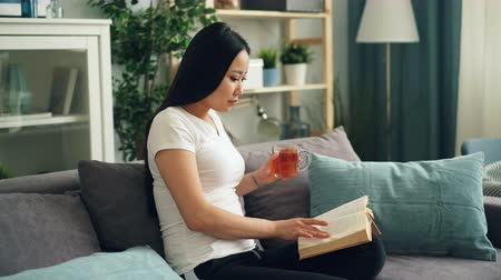 stories : Good-looking Asian woman is reading book enjoying modern literature sitting on sofa at home drinking tea and relaxing. Education, millennials and house concept.