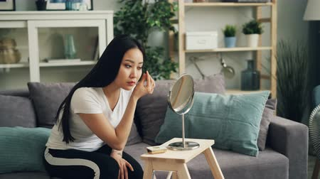brow : Beautiful Asian girl is putting on make up using mascara and face powder looking at mirror sitting on sofa at home. Beauty, young people and lifestyle concept.