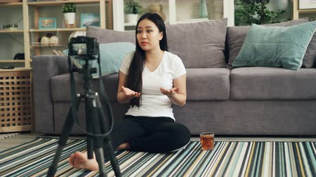 vlogging : Beautiful young woman cheerful vlogger is talking and gesturing recording video with camera for internet blog. Girl is wearing casual clothing and sitting on the floor. Stock Footage