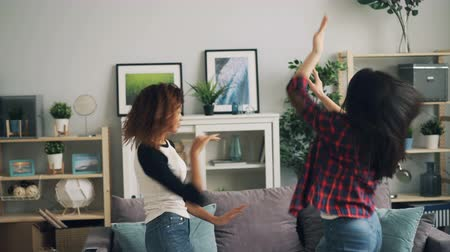 descuidado : Cute girls in trendy jeans are dancing at home together listening to music and having fun. Multiracial friendship, modern lifestyle and carefree youth concept.