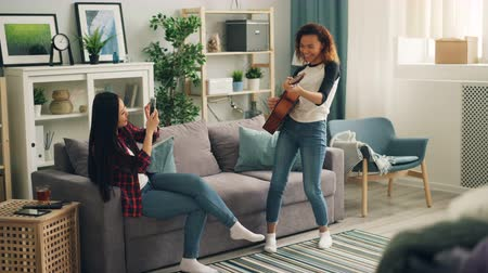 amatőr : Cute African American woman is playing the guitar at home while her Asian friend is recording video with smartphone and smiling enjoying music and friendship. Stock mozgókép