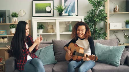 dal : Female friends are having fun at home, African American girl is playing the guitar and Asian young woman is recording video with smartphone. Friendship and music concept.