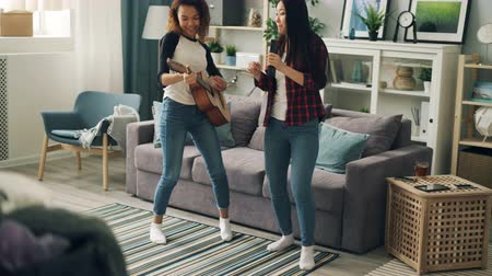 descuidado : Cute young ladies Asian and African American are singing in remote control and playing the guitar relaxing at home expressing positive emotions. Friendship and fun concept.