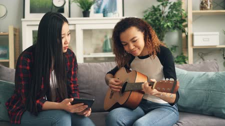репетитор : Mixed race friends Asian and African American are learning to play the guitar using tablet. Girls are looking at screen and trying finger positions on musical instrument.