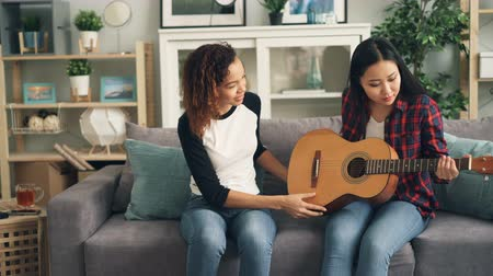 репетитор : Cheerful African-American girl is teaching her Asian friend to play the guitar at home. Young women are sitting on sofa holding musical instrument and talking.