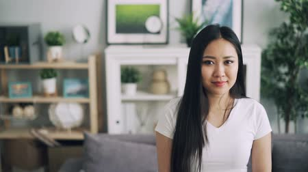duyarlı : Slow motion portrait of adorable Asian lady with beautiful smile standing in nice room, smiling and looking at camera. Stylish furniture and plants are visible.
