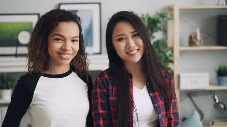 optimistický : Slow motion portrait of pretty students mixed-race friends Asian and African American looking at camera and smiling standing indoors at home together.