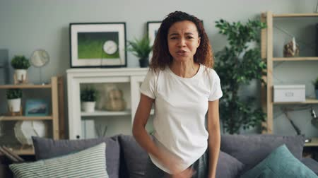 expressing negativity : Portrait of angry African American woman yelling and gesturing expressing negative emotions standing in modern apartment. Human feelings and people concept.