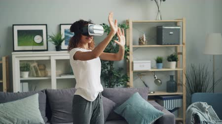 inovador : Young African American woman is enjoying experience with augmented reality glasses wearing modern vr headset. Girl is moving hands and head standing at home.