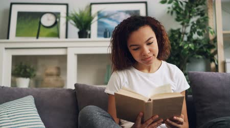 poezja : Good-looking African American student is reading book and smiling then turning page sitting on comfortable sofa alone in nice light apartment. Youth and education concept.