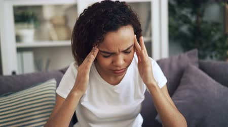 хмурый : Attractive African American girl is suffering from headache touching her head massaging temples sitting indoors at home. Pain, youth and health concept.