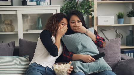 klick : Emotional young women are watching horror film together hiding behind pillows and closing eyes. Girls are eating popcorn sitting on sofa in modern apartment.