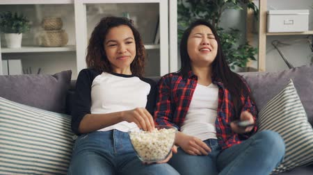 tv channel : African American and Asian young ladies are enjoying comedy on TV at home, laughing, talking and eating popcorn relaxing on sofa. Entertainment and food concept.