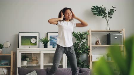 enjoyable : Playful African American woman is jumping dancing on couch at home listening to music with headphones enjoying rhythm and melody. Youth lifestyle and culture concept.