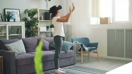 percepção : Slender young lady in casual clothing is using augmented reality glasses standing in light room at home and moving hands touching air. Devices and entertainment concept.