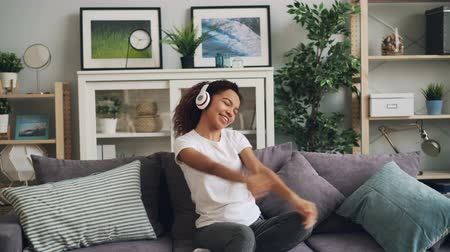 enjoyable : Cute African American girl is listening to music using headphones, singing and dancing sitting on couch in modern apartment. Beautiful people and hobby concept. Stock Footage