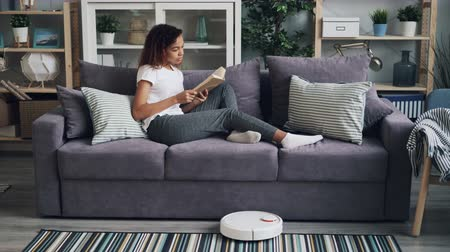 домашнее хозяйство : Relaxed African American girl is reading book resting on sofa while robotic vacuum cleaner is hoovering floor in house instead of person. Gadgets and household concept.