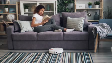 literatuur : Modern African American lady is turning on robotic vacuum cleaner then reading book sitting on sofa while robot is doing housework cleaning floor and carpet.