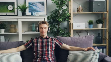 flat head : Zoom-in of happy guy melomaniac putting on headphones and listening to music and smiling enjoying melody and rhythm sitting on couch. Youth culture and lifestyle concept. Stock Footage