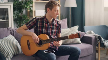 настройка : Young musician is tuning acoustic guitar touching strings sitting on couch at home during leisure time. Youth lifestyle, apartments and music concept.