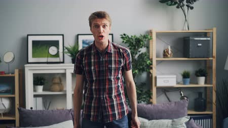 napětí : Portrait of angry young man shouting and gesturing expressing strong negative emotions standing in modern house and looking at camera then walking away.