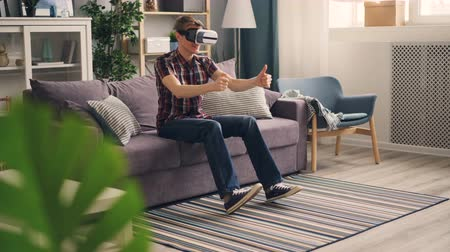 percepção : Carefree student is playing game with virtual reality glasses driving car racing sitting on sofa at home and moving hands and legs. Leisure and fun concept. Stock Footage