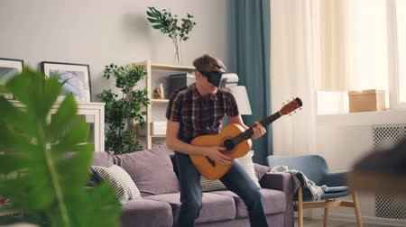 percepção : Funny teenager is having fun with virtual reality glasses wearing headset holding the guitar and moving body as if performing on stage. Nice interior is visible.
