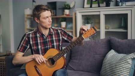 tuning : Male guitarist is tuning acoustic guitar checking sound touching strings sitting on sofa at home. Youth culture and lifestyle, apartments and music concept. Stock Footage