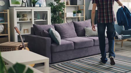 coming home : Tired guy is coming home throwing jacket on armchair and lying on couch relaxing and enjoying rest and peace. Nice apartment and comfortable furniture is visible. Stock Footage