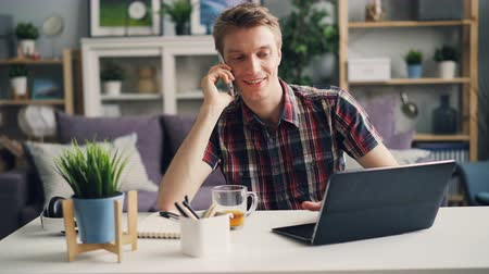 small businessman : Cheerful guy is talking on mobile phone and using laptop working at home doing distant work. Modern technology, communication and occupation concept.