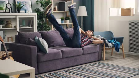 alojamento : Tired young man is coming to modern apartment throwing clothes on armchair then relaxing on couch lying and stretching enjoying rest after hard day at work. Vídeos