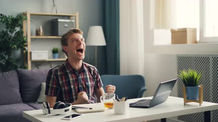 small businessman : Happy freelancer is working at home with laptop then laughing and gesturing espressing positive emotions enjoying his achievements. Modern technology and success concept. Stock Footage