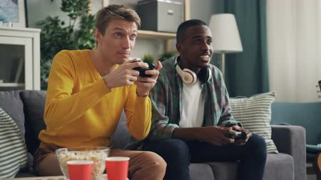 suceder : Male friends are enjoying video game playing together at home holding joysticks and trying to succeed. Men are expressing emotions and are concentrated on activity.