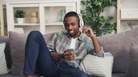 рэп : Cheerful African American guy is singing and listening to music in headphones relaxing on couch in modern apartment enjoying song. Youth culture and lifestyle concept. Стоковые видеозаписи