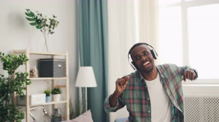 iyi bir ruh hali : Happy man African American dancer is having fun at home listening to music in headphones and dancing clapping hands. Youth lifestyle and millennials concept. Stok Video