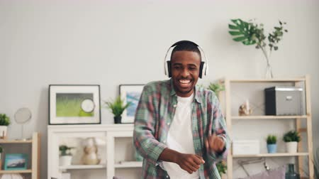 хорошее настроение : Joyful African American student is dancing singing and listening to music through wireless headphones relaxing at home. Youth culture and lifestyle concept.
