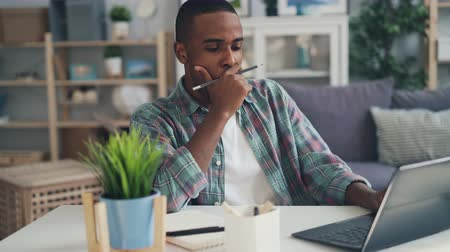 flat head : Tired, stressed and sleepy freelance worker African American guy is using laptop working at home and yawning feeling fatigue. Millennials and hard work concept.