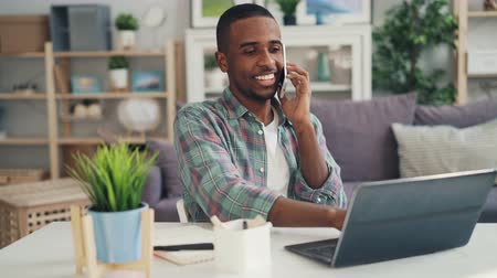 em casa : Cheerful African American freelancer is talking on mobile phone and using laptop working at home doing distant work. Modern technology, connection and occupation concept. Stock Footage