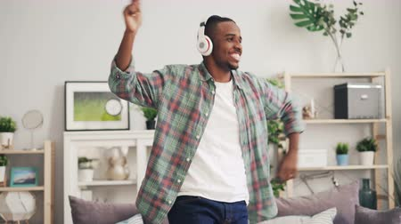 jó hangulatban : Cheerful African American man is dancing and laughing listening to music with headphones enjoying free time at home in modern apartment. Entertainment and gadgets concept.