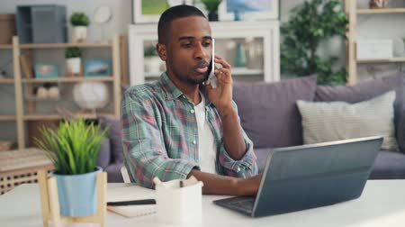 distante : Young African American specialist is talking to business contacts on mobile phone laughing and working with laptop enjoying distant work. Youth and lifestyle concept. Stock Footage