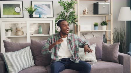 рэп : Happy African American guy is dancing and singing listening to music through headphones sitting on couch at home relaxing enjoying leisure time. Millennials and happiness concept. Стоковые видеозаписи