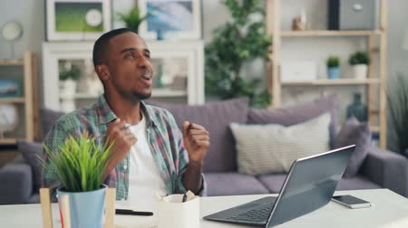 distante : Happy freelancer is working at home with laptop then laughing and gesturing espressing positive emotions enjoying his achievements. Modern technology and success concept. Stock Footage