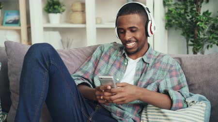 hírnök : Young African American man is using smart phone sitting on couch in apartment and listening to music through headphones. Devices and lifestyle concept.