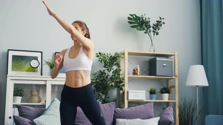 squatting : Pretty young sportswoman is practising at home raising arms and squatting enjoying activity and solitude. Modern youth, healthy lifestyle and interior concept. Stock Footage