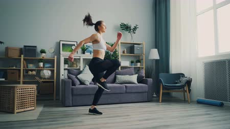 move well : Sporty young woman is running on the spot at home practising alone enjoying healthy activity and training legs and body. Active youth, sports and house concept.