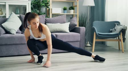 エネルギッシュな : Attractive young woman in trendy sportswear leggings, top and sneakers is training at home stretching legs on floor. Fit people, sports and leisure concept.