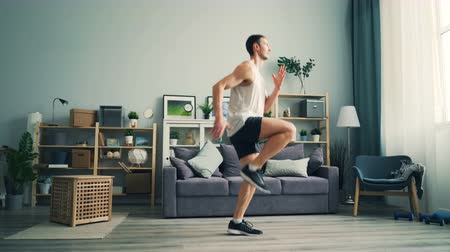 move well : Sporty young man is running on the spot at home practising alone enjoying healthy activity and training legs and body. Youth, cardio sports and house concept.